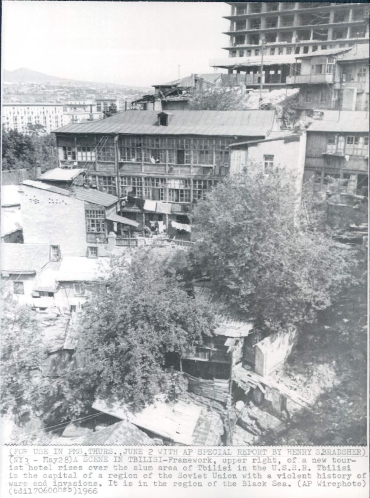 "Describing them as a ""slum,"" an American press photo from 1966 shows several dilapidated houses in Tbilisi covered in homebuilt extensions as a new hotel looms in the background. Credit: Associated Press."